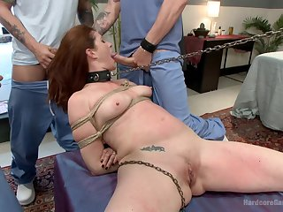 Redhead gets gagged by dicks while sitting tied in the air in ropes